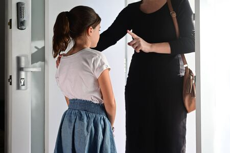 Mother warning her daughter (age 10) how to behave before she live home. Standard-Bild