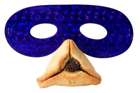 Purim party mask on traditional Jewish cookie pastry (Ozen Haman Hamantashen) on Purim Jewish holiday. Isolated on white background. No people. Copy space