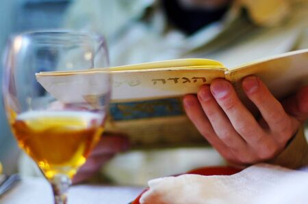 Jewish man reads the Haggadah. The Haggadah is a Jewish text that sets forth the order of the Passover Seder on Passover Jewish Holiday.