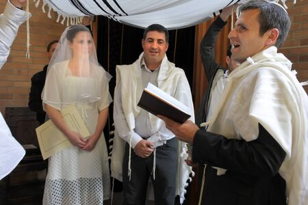 Rabbi blessing Jewish bride and a bridegroom in modern Orthodox Jewish wedding ceremony in synagogue.Real people. Copy space