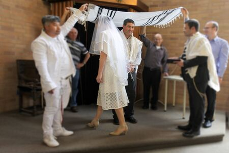 Jewish bride circling seven time around her bridegroom in a modern Orthodox Jewish wedding ceremony in synagogue. Real people. Copy space