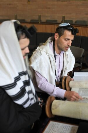 Jewish men reading and praying from a Torah scroll in synagogue . Standard-Bild