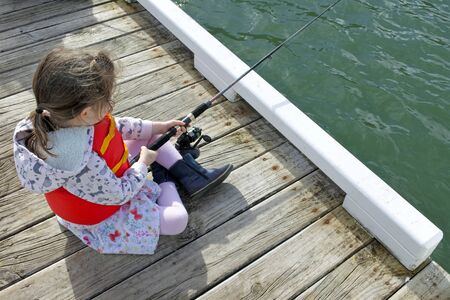 Young girl (age 06) holding a fishing rod fishing from a boat jetty.Real people. Copy space