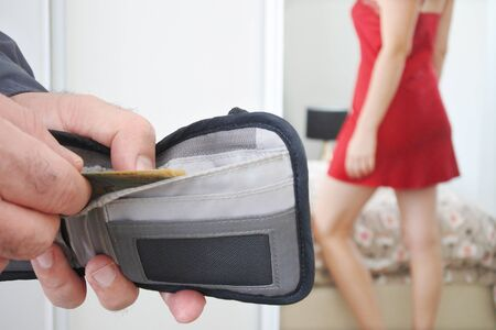 Man paying prostitute woman for sex - prostitution and escort concept Stock Photo