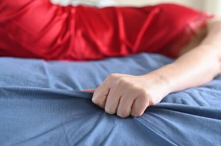 Sexy woman having an orgasm in bed.Close up view of hand grabbing sheet.