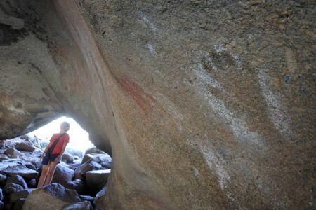 Young Australian tourist girl (age 9-10) looking at ancient Aboriginal Australian indigenous rock painting in Mulkas Cave near Hyden Western Australia. Reklamní fotografie