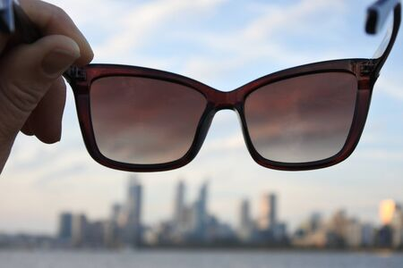 POV (point of view) of a person standing on Swan River riverbank holding sunglasses looking at the landscape view of Perth city financial centre skyline at sunset in Western Australia.
