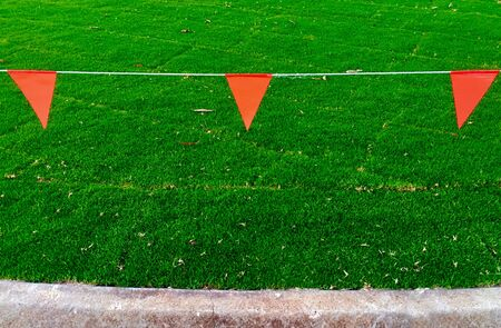 A warning red triangular shape flags hanged on a wire to protect new installed fresh natural green grass rugs. 写真素材