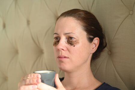 Adult woman (age 35-40)  relaxing at home with coffee grounds on her face to help to clear away dead skin cells and unclog the pores. Stockfoto
