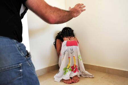 Young girl victim of domestic violence hide in the corner from a violence male.