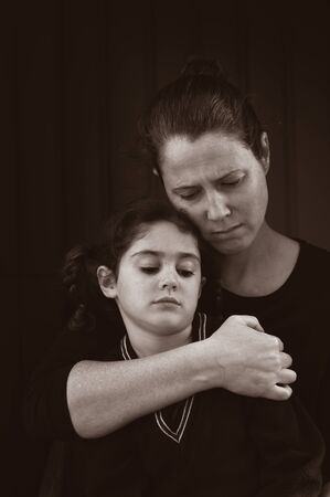 Sad mother and daughter sitting in the dark looking away from camera isolated on black background. Archivio Fotografico