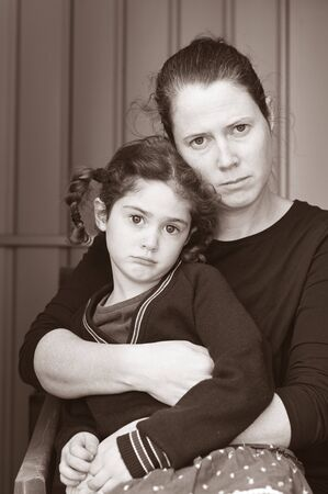 Poor mother and daughter looking at camera isolated on black background. Foto de archivo