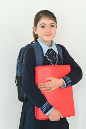 Young schoolgirl (age 10) dressed in school uniform carry a school bag and a folder is ready to go to school.