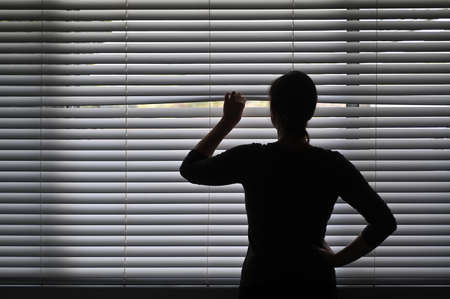Suspicious adult woman looking outside home window from behind Venetian curtains. Concept photo of person that have Pistanthrophobia and Agoraphobia, a person who don't trust fear of leaving the house.
