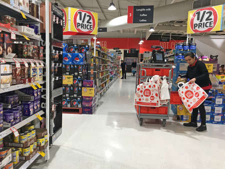 Coles grocery employee stacking items into a cart for online pickup/delivery options.Over 5 million Australian grocery buyers (31%) will consider buying groceries online next year. Editorial