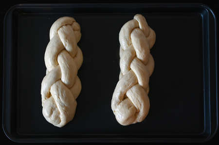 Flat lay of two uncooked challah sweet bread on a baking tray.