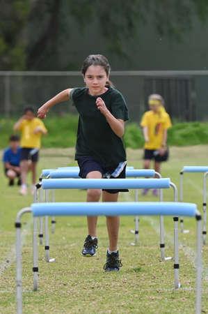 Young girl (age 10) runs a hurdle.