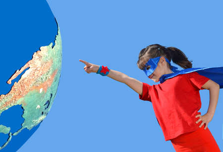 Young superhero child (girl age 05) pointing at planet Earth make believe play pretend  saving the world. Concept photo of earth day and world environment protection. Real people. Copy space