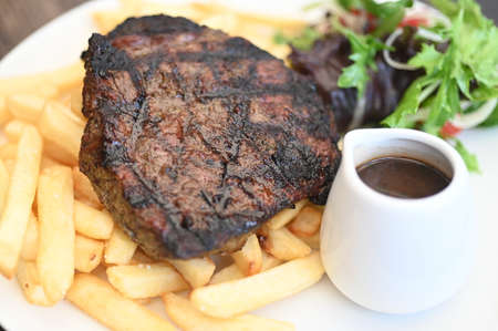 Well done steak served with potatoes chips salad and gravy close up background