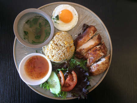 Vietnamese food roasted chicken served with rice, egg ,salad and soup. Reklamní fotografie