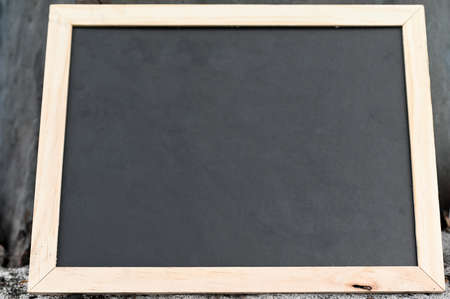 Blank chalkboard with wooden frame leaning on a tree outdoors.
