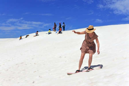Adult Australian woman sliding down with a snowboard on Lancelin sand dunes near Perth in Western Australia.