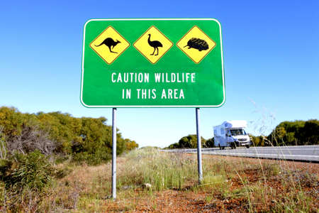 PERTH - OCT 04 2020:Motorhome passing by a large sign reading caution wildlife in the area.About four million Australian mammalian roadkill per year.