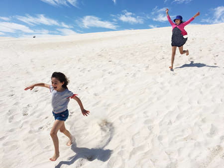 Happy young Australian girls (age 6 and 10) running down on Lancelin sand dunes near Perth in Western Australia. Reklamní fotografie