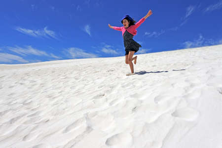 Happy young Australian girl (age 10) running down on Lancelin sand dunes near Perth in Western Australia.