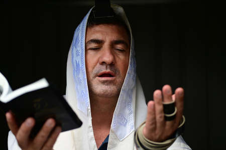 Adult Jewish man holding Siddur book (Jewish prayer book) , wearing tallit and tefillin (Jewish prayer clothing), paying the morning pray.Isolated on black background. Real people. Copy space