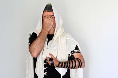 A Jewish man wearing Tallit (prayer shawl) praying with Tefillin (phylacteries) on morning prayers.