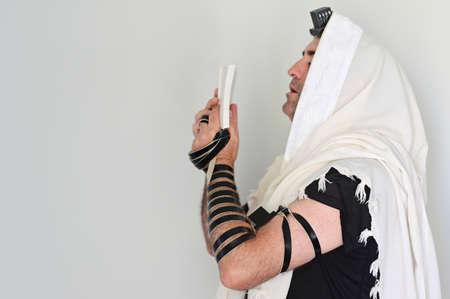 A Jewish man wearing Tallit (prayer shawl) praying with Tefillin (phylacteries) on morning prayers.