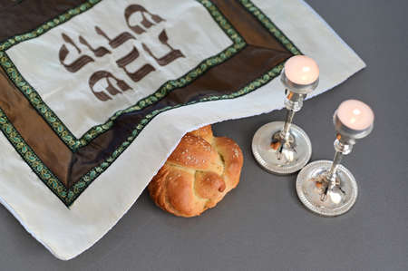 Challah (special Jewish bread) and two lit candles on Sabbath eve Jewish Holiday (Judaism's day of rest on the seventh day of the week Stock Photo