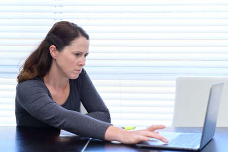 An upset adult woman (age 30-40) using laptop looking at negative financial data on laptop.
