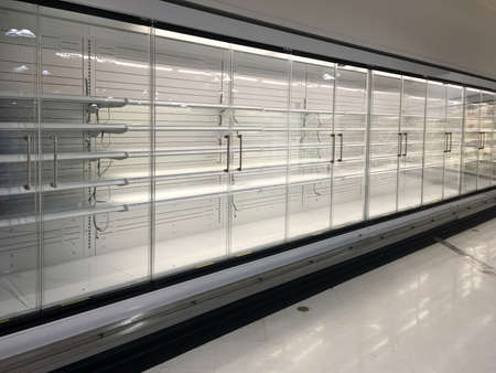 Row of empty commercial fridges at grocery store