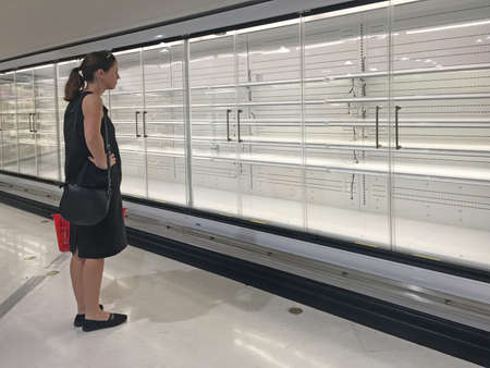 Upset adult woman (age 30-40) looking at Row of empty commercial fridges at grocery store.
