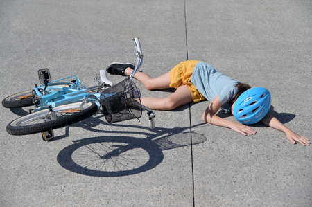 Young girl (female age 10-11) fallen of a bicycle laying down beside her bike unconscious on paved road. Above view. Real people. Copy space Stock fotó
