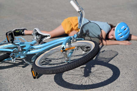 Young girl fallen of a bicycle laying down beside her bike unconscious on paved road. Real people. Copy space Stock fotó