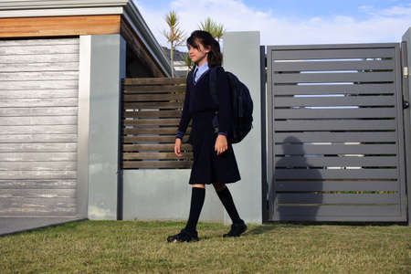 Young schoolgirl (female age 10-11) going to school from home.