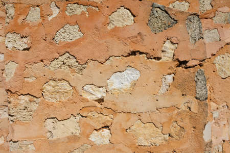 A old wall made out of mud and stones, solid and durable construction material.Abstract background and texture.