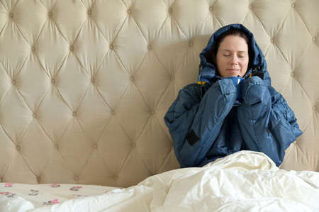 Happy adult woman wearing a very warm clothing and covered with a blanket, sitting on a  double bed, having a hot drink in bedroom  on a cold winter day.