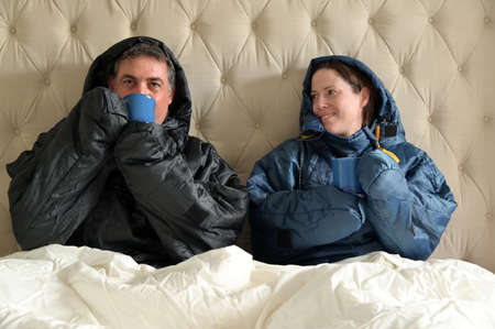 Happy couple sitting side by side wearing a very warm clothing and covered with a blanket, sitting on a  double bed, having a hot drink in bedroom  on a cold winter day.
