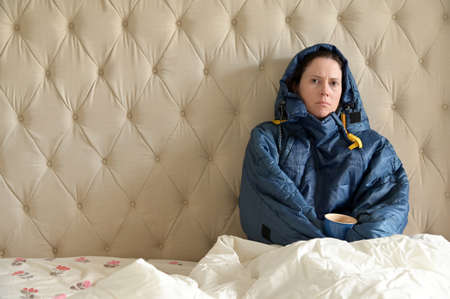Sad adult woman wearing a very warm clothing and covered with a blanket, sitting on a  double bed, having a hot drink in bedroom  on a cold winter day. Stock fotó