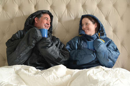 Happy couple sitting side by side wearing a very warm clothing and covered with a blanket, sitting on a  double bed looking at each other, having a hot drink in bedroom  on a cold winter day.