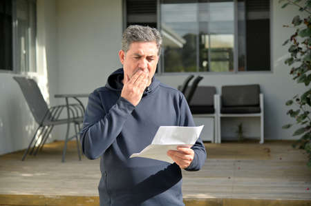 Shocked mature adult man (male age 40-50) reading a letter outside a home front door. Stock fotó