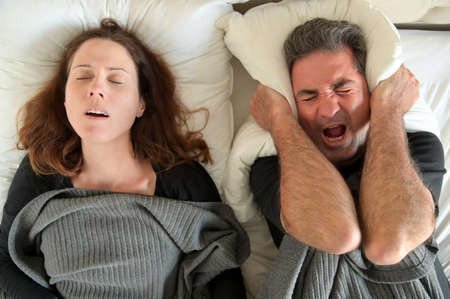 Upset mature adult man (male age 40-50) suffering from his partner an adult woman (female age 30-40)  that snoring during sleep in bed. Couple lifestyle and people health care concept. Stock fotó