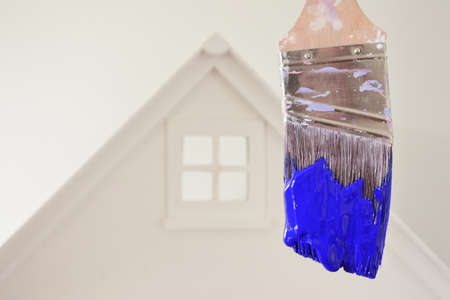 Paint brush with blue paint color against a white house. Renovation, home decoration and painting house concept. No people. Copy space