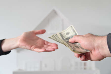 Two people (male and female) passing money against a white house. Mortgage, housing market, home loans and property, management concept. No people. Copy space Stock fotó