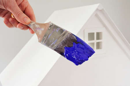 Person holding a paint brush with blue paint color against a white house. Renovation, home decoration and painting house concept. No people. Copy space