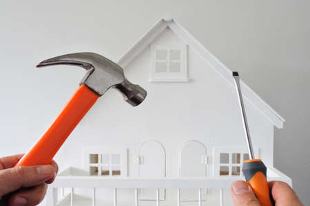 POV (point of view) of a person holding a hammer and screwdriver against a white house. Renovation, home decoration and painting house concept. No people. Copy space Stock fotó